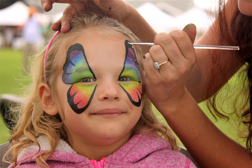 SPAT SummerFair in Wellfleet Five year-old Jessie Williams of Putnam, Connecticut, transformed into a butterfly with Andrea Howard's flair from Color Pop, photo by William F Pomeroy
