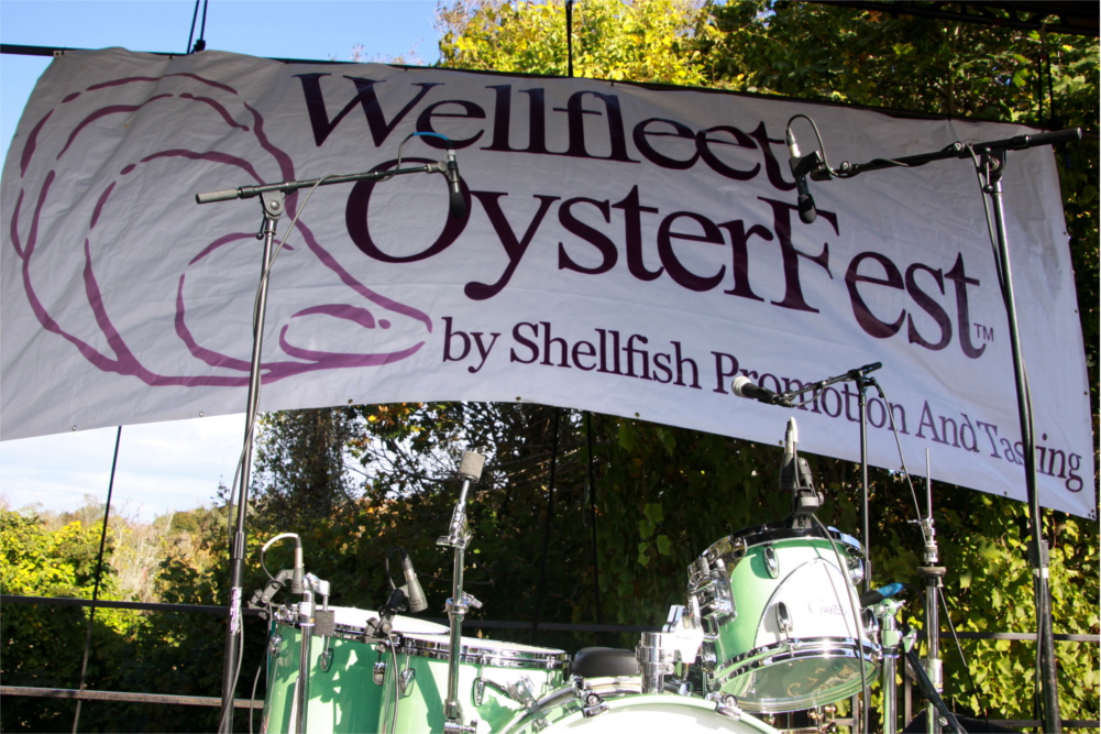 Wellfleet OysterFest banner and drums awaiting band on the music stage