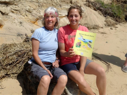 Two women sitting on beach holding book called Barrier Beach Bums