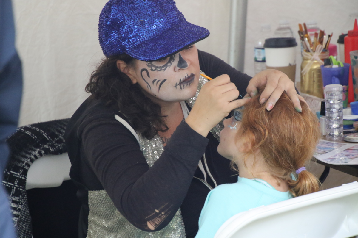 Woman with face painted, painting a girl's face in the Family Fun area