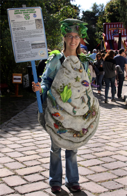 Woman at OysterFest Dressed as Human Oyster holding recycling sign