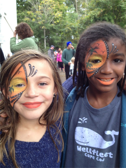 Two smiling girls with faces painted at the OysterFest