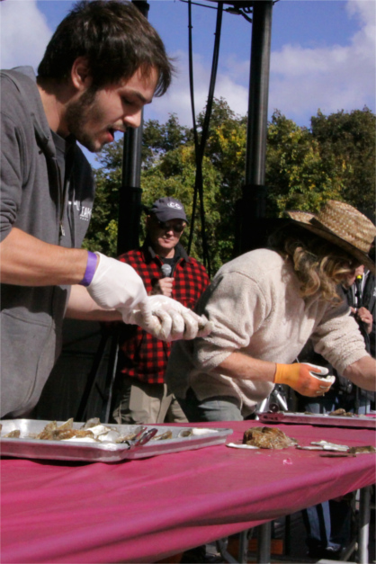 Two Shuckers Shucking at Shucking Table On Stage at Wellfleet OysterFest Shucking Contest