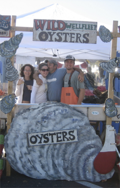Sign with 'Wild Wellfleet Oysters' above Nate Johnson's Raw Bar and Four Smiling Shuckers